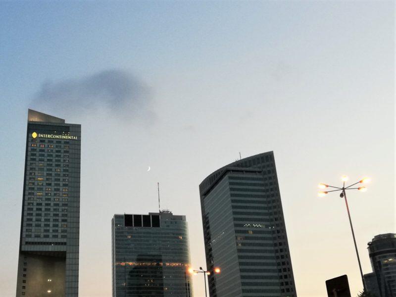 Na jasnym niebie sierp księżyca między wieżowcami centrum Warszawy