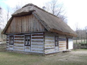 Drewniana chata kryta strzechą.